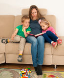 Mother reading a story book to her cildren on a couch in living. Room Royalty Free Stock Images
