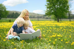 Mother Reading Story Book to Two Young Children Outside in Meado Royalty Free Stock Photos