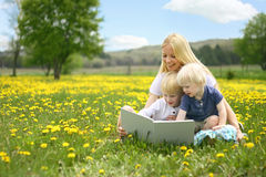Mother Reading Story Book to Two Young Children Outside in Meado. A happy young mother is sitting outside in a meadow of yallow Dandelion flowers, reading a royalty free stock images