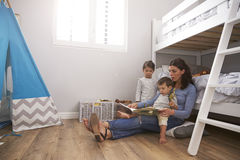 Mother Reading Story To Children In Their Bedroom Stock Photography