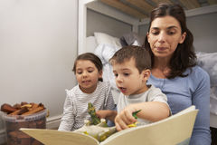Mother Reading Story To Children In Their Bedroom Stock Photos