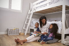 Mother Reading Story To Children In Their Bedroom Stock Photo