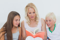 Mother reading a story to her children Stock Photos