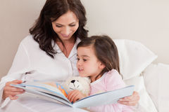 Mother reading a story to her daughter. In a bedroom Royalty Free Stock Photo