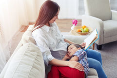 Mother reading a story to her son Stock Photos