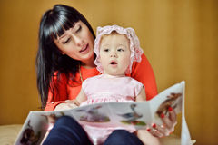 Mother reading to baby girl Stock Images