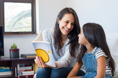 Mother reading to child. Happy mother reading story book to little girl. Happy latin mother and daughter reading a book while sitting on couch at home. Mother Royalty Free Stock Photos