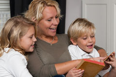 Mother reading to children stock images