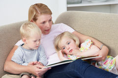 Mother Reading To Children At Home Stock Photo
