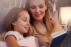 Mother reading to daughter Stock Photos