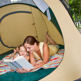 Mother reading to daughter in tent Stock Image