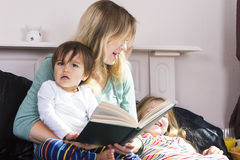 Mother reading to kids in bed Stock Images