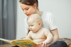 Mother reading to little infant colorful book with fairy tales. Little toddler listens attentively to his mom and watch pictures in textbook Stock Images