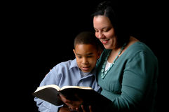 Mother Reading to Son. Mother reading the Bible to young son over a black background