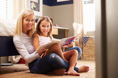 Mother reading with young daughter Stock Photo