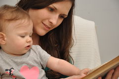 Mother reads a book to a baby daughter Stock Photos