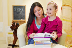 Mother reads book to daughter sitting at table Stock Photos