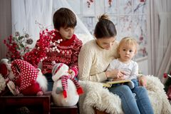 Mother reads book to her sons, children sitting in cozy armchair on a snowy winter day. Wintertime royalty free stock images