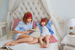 Mother reads a book to little daughter on a bed Royalty Free Stock Photo