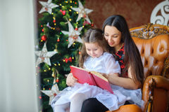 Mother reads fairy tales to the little daughter. Stock Photo