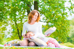 Mother reads her daughter's interesting book Royalty Free Stock Images