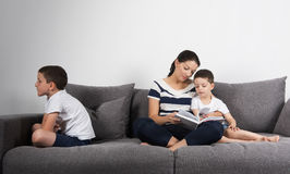 Mother reads an interesting book with her sons. Jealousy concept. Royalty Free Stock Photography