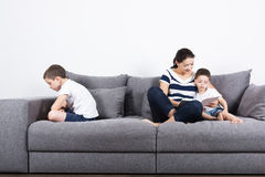 Mother reads an interesting book with her sons. Jealousy concept. Mother reads an interesting book with her son, and another son is offended on the opposite stock photo