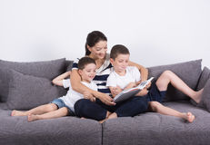 Mother reads an interesting book with her sons of the sofa. Royalty Free Stock Photo