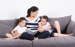 Mother reads an interesting book with her sons of the sofa. Studio portrait on white background Royalty Free Stock Photo