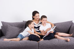 Mother reads an interesting book with her sons of the sofa. Studio portrait on white background Royalty Free Stock Photos