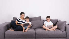 Mother reads an interesting book with her sons of the sofa. Studio portrait on white background Stock Photo