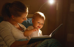 Mother reads to baby book in bed Royalty Free Stock Photography