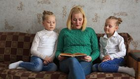 Mother reads two daughters a book stock footage