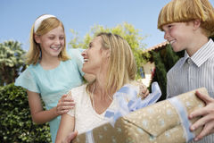 Mother Receiving Gift From Children Outdoors Royalty Free Stock Images