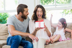 Mother receiving a gift from her husband and daughter Royalty Free Stock Image