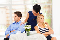 Mother reconciling couple. Caring mother reconciling fighting young couple Royalty Free Stock Images