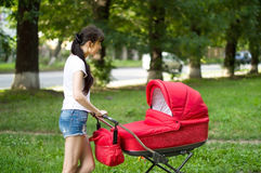Mother with a red baby carriage on walk Royalty Free Stock Photo