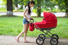 Mother with a red baby carriage on walk Royalty Free Stock Photography