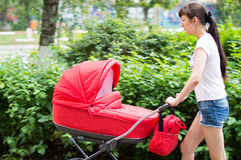 Mother with a red baby carriage on walk Royalty Free Stock Image