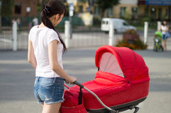 Mother with a red children's carriage crosses the road Royalty Free Stock Photography