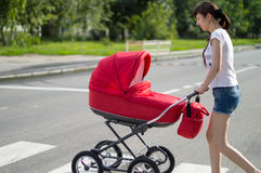 Mother with a red children's carriage crosses the road Stock Image