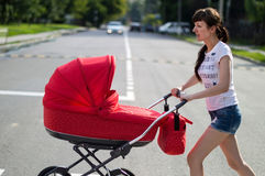 Mother with a red children's carriage crosses the road Royalty Free Stock Image