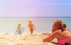 Mother relax while kids play with water at beach Stock Photography