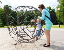 Mother rescues her little son from the sphere cage Royalty Free Stock Photography