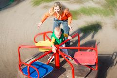 Mother riding her little son on a swing.Circling at high speed.A happy weekend. A happy weekend.Mother riding her little son on a swing.Circling at high speed royalty free stock photography
