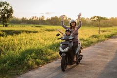 Mother riding motorcycle with daughter stock image