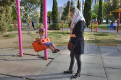 Mother rocking little boy on swing in park, Shiraz, Iran. Fars Province, Shiraz, Iran - 19 april, 2017: Playground in a city recreation park, a young muslim Stock Image