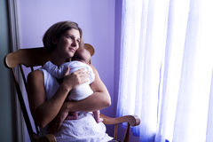 Mother rocking newborn baby by window Stock Photo