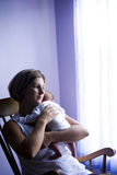 Mother rocking newborn baby by window Royalty Free Stock Images
