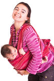 Mother rocks baby to sleep in sling Stock Photos